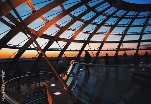 Fotografie, Obraz People Standing By Railing In Modern Building During Sunset