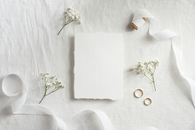 Wedding Invitation Card Template. Top View Blank Paper Card, Ribbon, Golden Rings, Flowers On White Background.