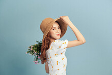 Close Up Portrait Of An Attractive Young Woman In Summer Dress And Straw Hat Holding Flower Bouquet And Looking Over Her Shoulder Isolated Over Blue Background