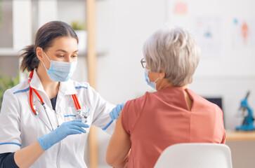 Panel Szklany Siatkówka Doctor giving a senior woman a vaccination