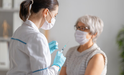 Fototapeta Boks Doctor giving a senior woman a vaccination
