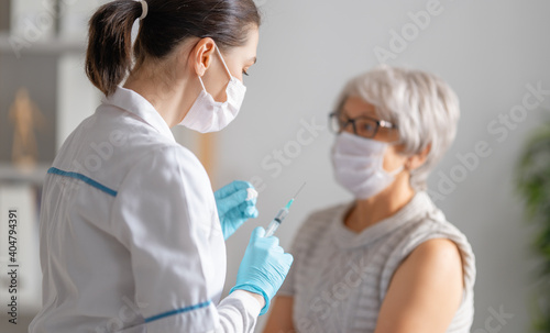 Canvas Print Doctor giving a senior woman a vaccination