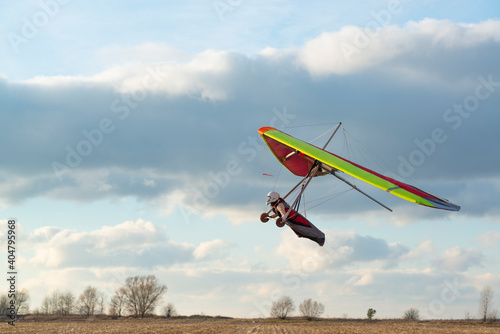 Brave girl learn to fly on the colorful hang glider wing. Fototapet