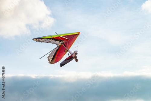 Billede på lærred Colorful beginner hang glider wing silhouette with blue sky on the background