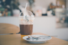 Transparent Plastic Glass Filled With Orange Juice On Ice And Blurred Plate , Little Piece Of Cake ,spoon With Blurred Coffee Shop Backgroundoffee Shop Background