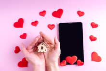 Hands Hold A Small Mock Up Of A Wooden House Over A Black Blank Screen Of A Tablet Or Phone With Red Heart Shape On A Pink Background. Greeting Card For Valentine's Day, Family Day, Mother's Day