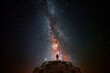 Man on top of a mountain observing the universe