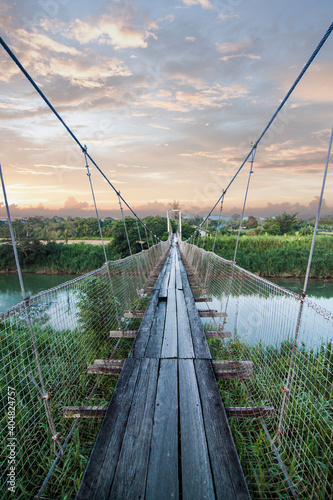 Canvas-taulu Empty Footbridge Over River During Sunset