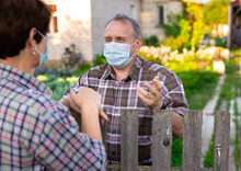 Farm Neighbors In Protective Masks Talk At The Border Of Garden Plot