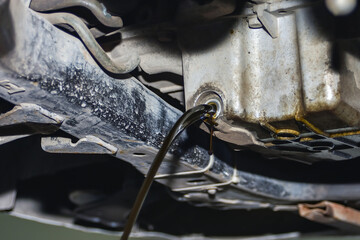 Dirty and used engine oil on a car drains from the engine sump i