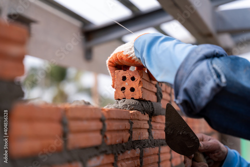 Fotomural Close up of Bricklayer worker installing brick masonry on exterior wall with tro