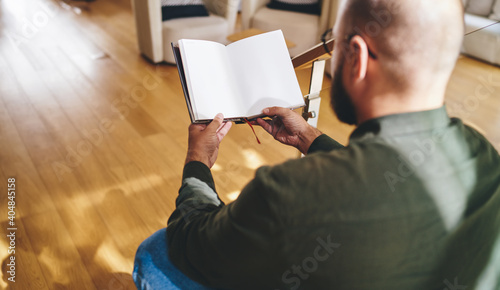Unrecognizable man reading book in modern apartment on weekend Wallpaper Mural