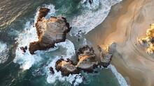 Vista Aérea De Olas Que Golpean Las Rocas En La Playa Y Huellas De Carro En La Arena