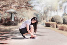 Woman Tying Shoelace While Crouching On Road