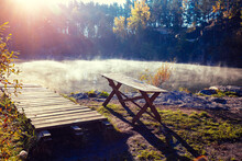 Wooden Pier And Wooden Table By The Lake On A Foggy Autumn Morning