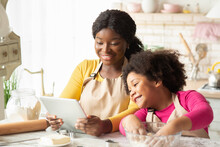 Black Mom And Little Daughter Checking Dough Recipe Online On Digital Tablet
