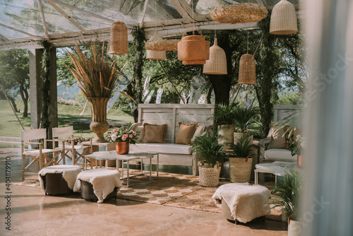Armchairs and garden table adorned with pots, flowers and imitation leather fabrics Fototapet