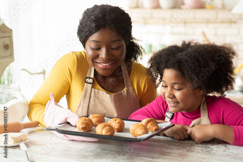Black mother and daughter holding tray with fresh baked croissants in kitchen Fototapete