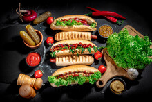 Grilled French Hot Dog And Hot Dogs With Different Toppings On Dark Background. Fast Food Concept