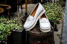 White Leather Moccasins. Photo On The Street Next To The Flowers. Trendy White Loafers. Fashionable Women's Leather Shoes.