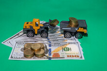 A Yellow Loader Is Scooping Coins To Put A Dump Truck On Dollar Bills And A Stack Coins, On A Green Background.