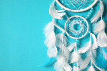 Beautiful Dream Catcher Hanging On Light Blue Background, Closeup. Space For Text