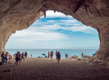 View From Inside Of Limestone Sea Cave At Cala Luna Beach, Sardinia, Italy With Group Of Tourist People Sunbathing And Takes Photos. Famous Touristic Destination