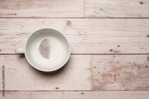Canvas Empty white mug cup with a tea bag in it waiting to be brewed with hot water on