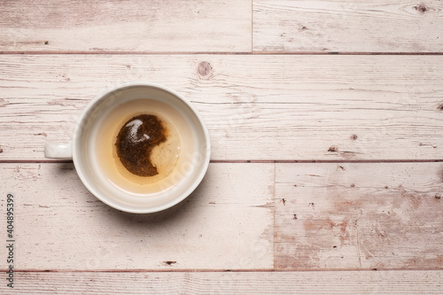 Obraz Partially filled and brewed cup of tea with a golden colour in a white mug on a textured white wooden table surface with copy space and room for text - fototapety do salonu