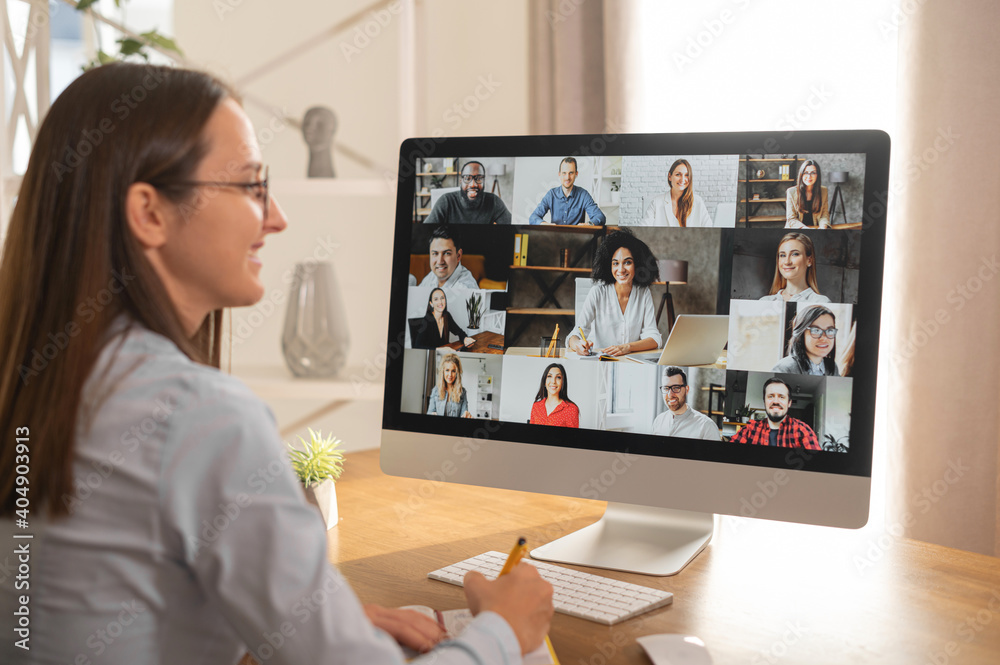 Fototapeta Group of diverse multiracial people on the laptop screen, a young woman is talking with colleagues, employees online. Video conference, brainstorm, webinar concept