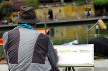 Rear View Of Artist Painting At Riverbank