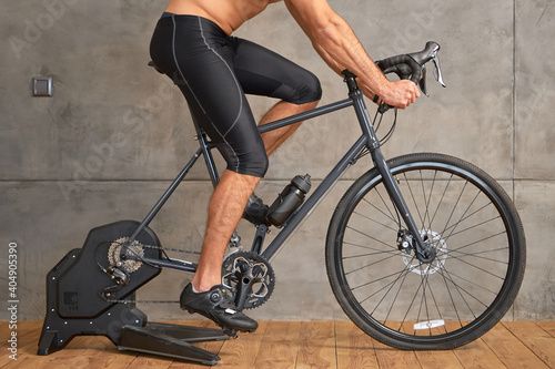 Tablou Canvas Athletic young man riding stationery bike at home
