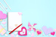Valentine hearts with blank notepad, pen and gift box on blue background
