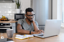 Tired African American Male Employee Sit At The Table In Home Office, Using Laptop, Smiling. Focused Exhausted Businessman Work On Own Project, Having A Tense And Ache In Back, Needing A Rest