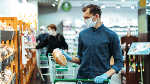 Fotografie, Obraz close up. young man buying bread in a supermarket.