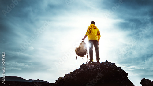 Fototapeta Young man with backpack standing on the top of a mountain at sunset - Goals and achievements obraz