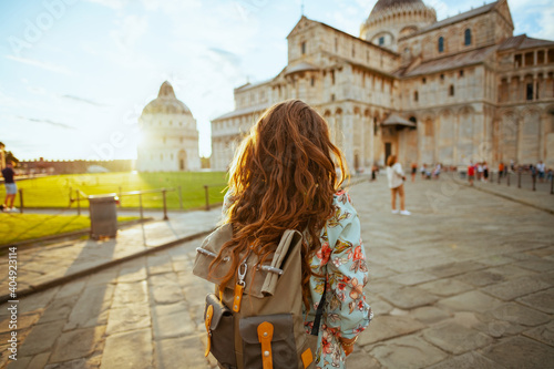 Fototapeta Seen from behind stylish woman in floral dress having excursion