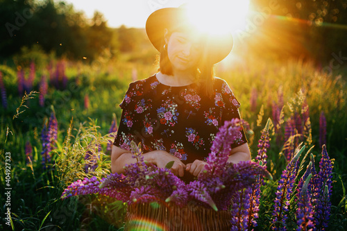 Canvas Beautiful woman relaxing in lupine field with rustic basket and flowers at sunse