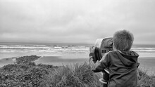Rear View Of Boy Looking Through Coin-operated Binoculars At Beach Against Sky