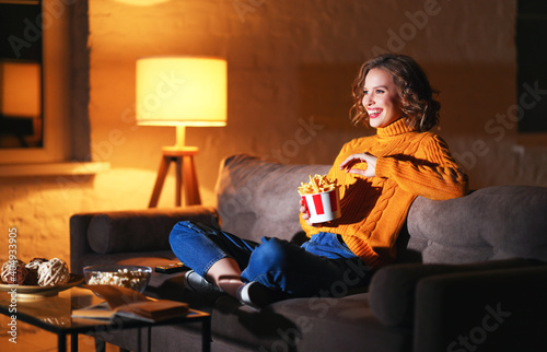 Obraz Excited female eating French fries and watching film - fototapety do salonu