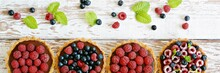 Raspberry And Blueberry Tartlets With Chocolate Ganache, Fresh Berries And Mint Leaves, Selective Focus. Fresh Fruit Tart On White Background, Freshly Homemade Fruit Cake On A Table