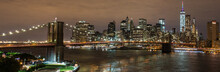 Panoramic View On Manhattan Skyline And Brooklyn Bridge At Night