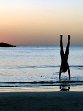 Silhouette Woman Doing Handstand At Beach Against Sky During Sunset