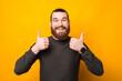 Leinwandbild Motiv Cheerful handsome bearded man standing over yellow background and showing thumb up.