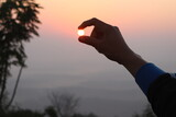 Optical Illusion Of Cropped Hand Holding Sun Against Sky During Sunset