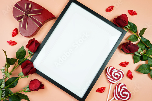 Happy Valentine's Day black border picture frame, styled with Valentine red roses, heart shape gift and lipstick kissess chocolates on a modern coral background. Mockup. Top view flat lay. Copy space.