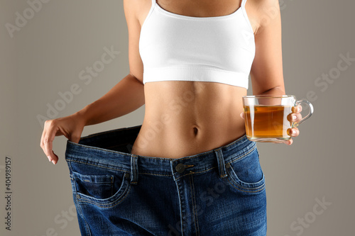 Obraz Young woman in old big jeans with cup of tea showing her diet results on beige background, closeup - fototapety do salonu