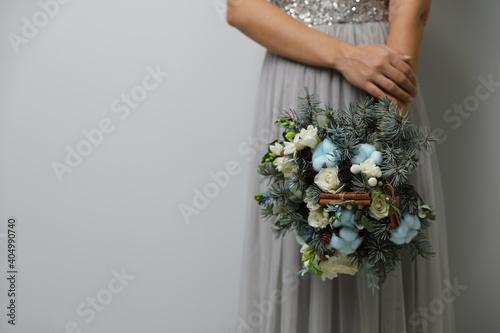 Fototapeta Bride holding beautiful winter wedding bouquet on light grey background, closeup