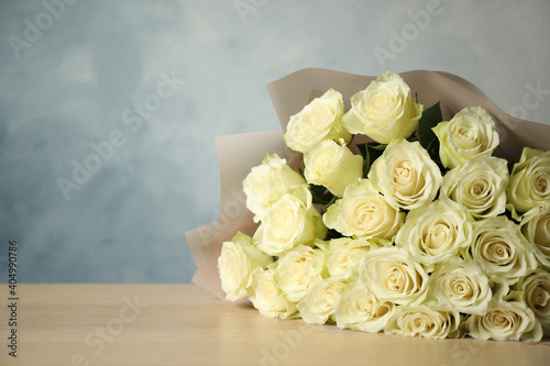 Obraz na plátně Luxury bouquet of fresh roses on wooden table, space for text