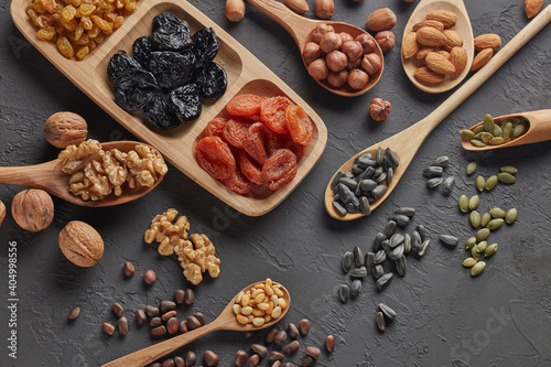 Fototapeta Different kinds of nuts, dried fruits in wooden spoones and dish on black slate background. Top view. Healthy food. Vegetarian nutrition obraz